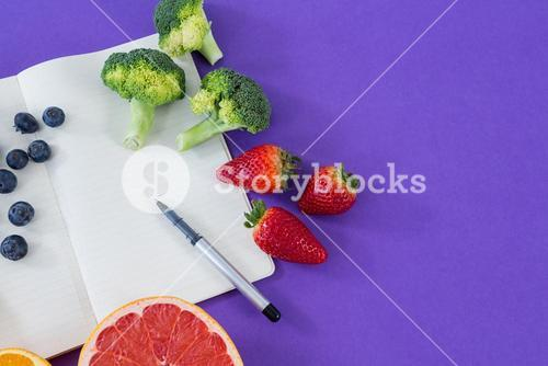 Measuring tape, various fruits, vegetable, opened book and pen