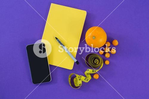 Mobile phone, book, pen, measuring tape and citrus fruit