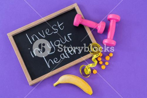 Dumbbell, banana, measuring tape and slate with text
