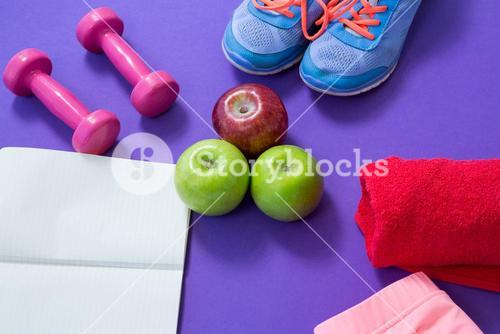 Fitness accessories with opened book and apples