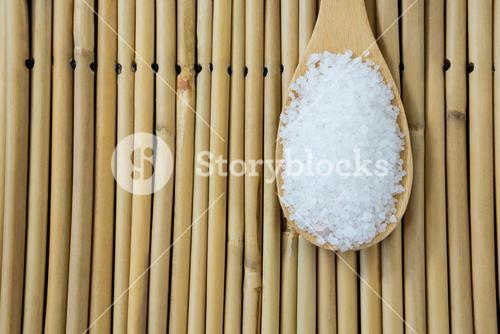 Salt in wooden scoop kept on bamboo mat