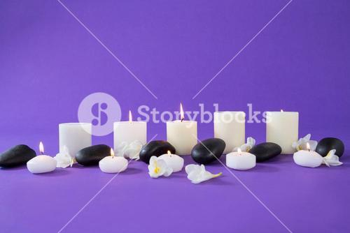Candles, flowers and zen stones on purple background