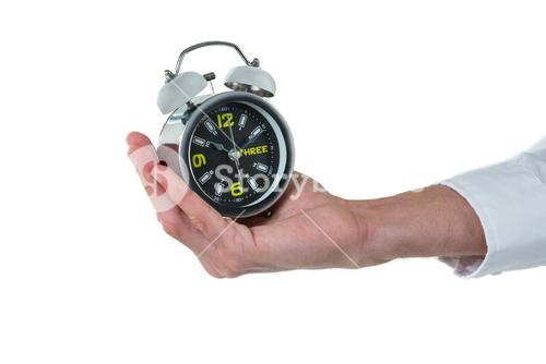 Hand of executive holding alarm clock