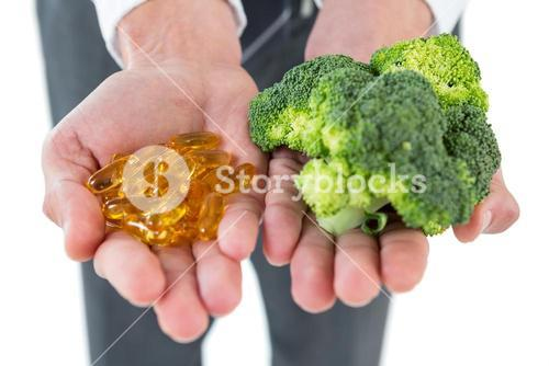Businessman holding broccoli and vitamin pills