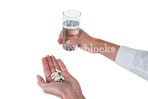 Executive holding glass of water and medicines