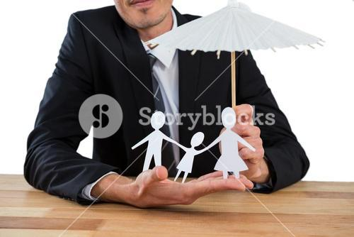 Businessman holding an umbrella protecting a family