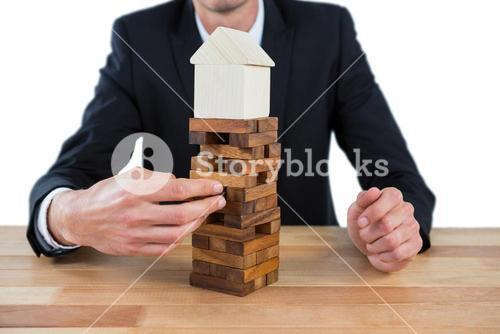 Businessman arranging building blocks with house model on top