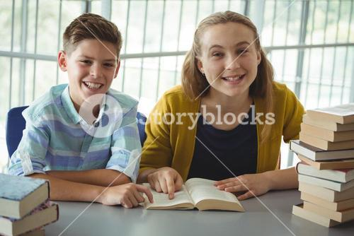 Smiling school kids reading books in library at school