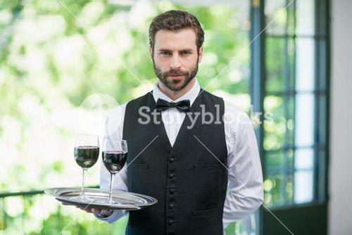 Male waiter holding tray with wine glasses