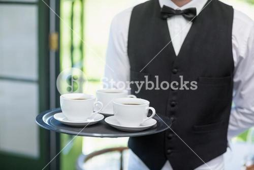 Male waiter holding tray with coffee cups