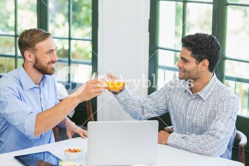 Happy executives toasting glasses of juice