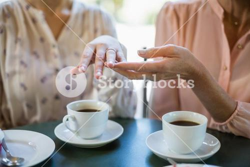 Woman showing engagement ring to her friend