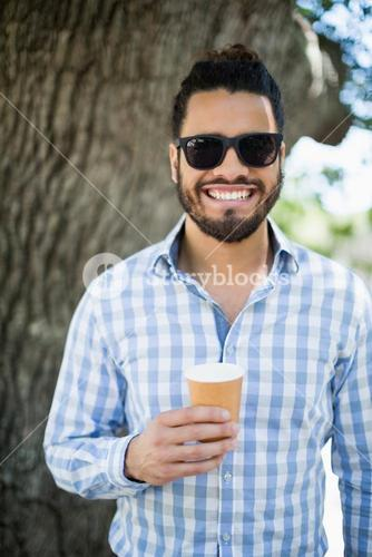 Handsome man in sunglasses holding disposable coffee cup in the park