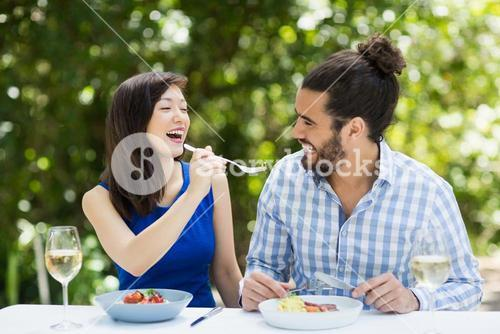 Woman feeding food to man