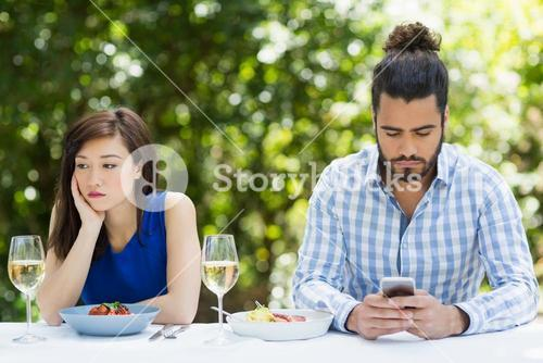 Man ignoring woman and using mobile phone