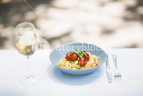 Wine glass with food in bowl and cutlery arranged on table