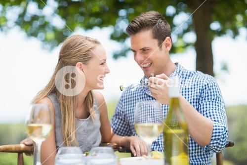 Man feeding food to woman