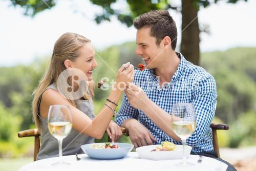 Happy couple feeding food to each other
