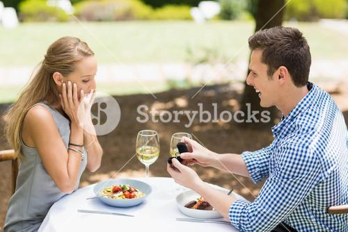 Man proposing to woman offering engagement ring