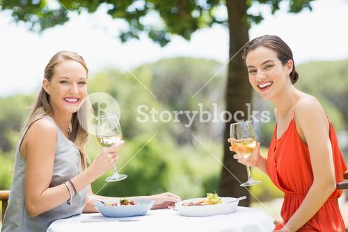 Happy friends holding glasses of wine in a restaurant