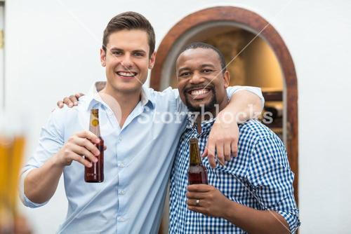 Friends hugging each other while holding beer bottles