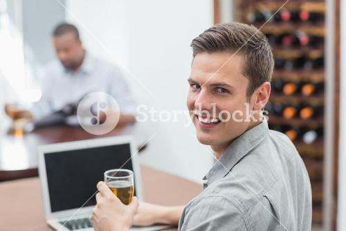 Handsome man holding beer glass while using laptop
