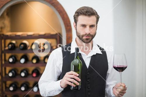 Male waiter holding wine glass and wine bottle in the restaurant