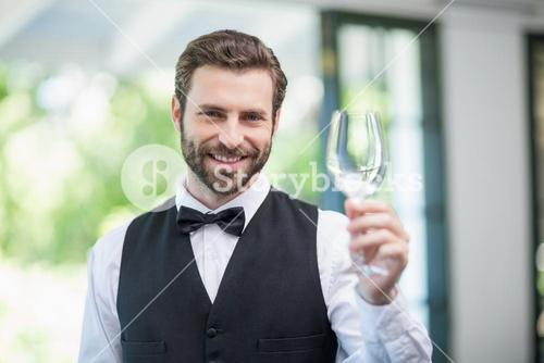 Male waiter holding empty wine glass in the restaurant