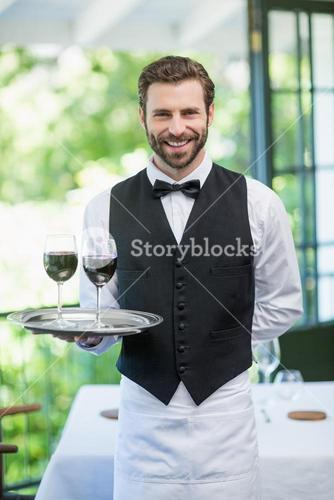 Male waiter holding tray with wine glasses in the restaurant
