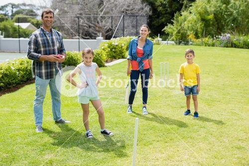 Family playing cricket in park