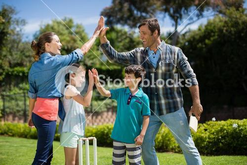 Family giving high five to each other while playing cricket