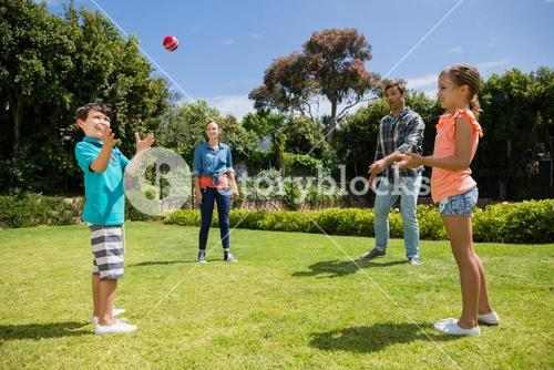Happy family playing with the ball in park