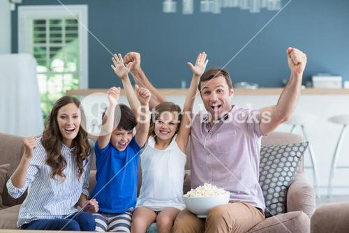 Family cheering while watching tv in living room at home