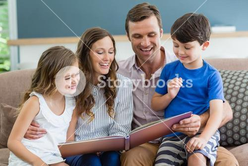 Family sitting on couch looking at photo album in living room at home