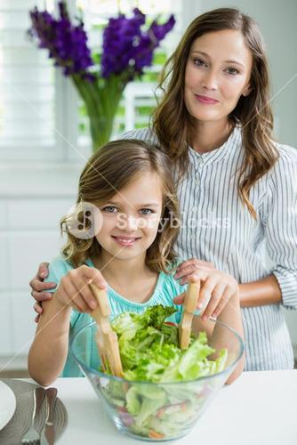 Portrait of smiling mother and daughter mixing bowl of salad in kitchen