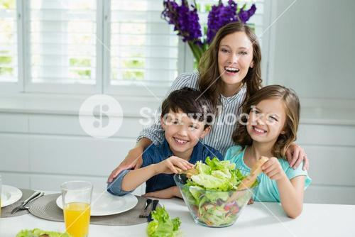 Smiling mother and childrens mixing bowl of salad in kitchen