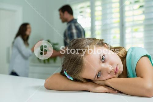Sad girl resting on table in living room at home
