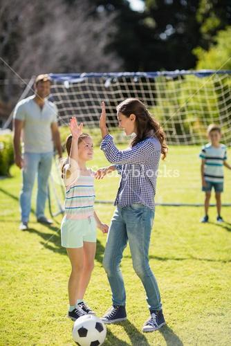 Mother and daughter giving high five while playing football in park