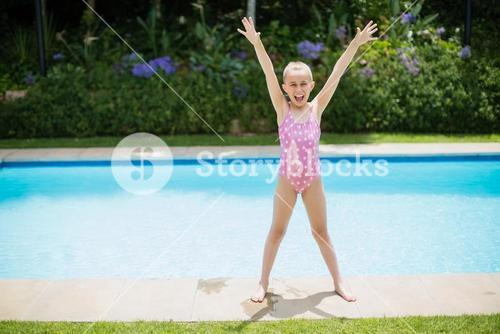 Girl standing with her hands raised near swimming pool