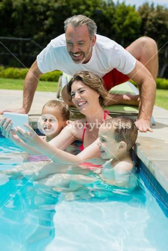 Smiling woman taking selfie with family in swimming pool