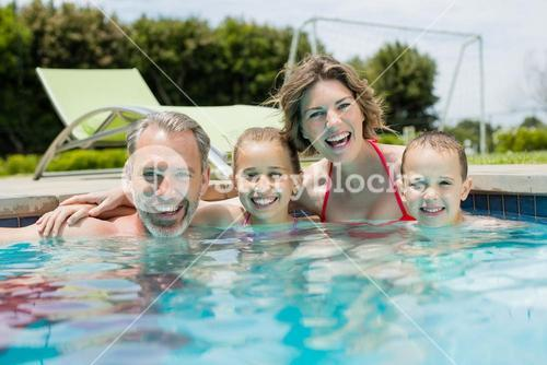Smiling family enjoying in swimming pool