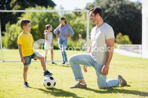Father and son playing football in park