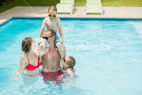 Happy parents and kids in pool