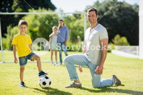 Father and son playing football in park on a sunny day