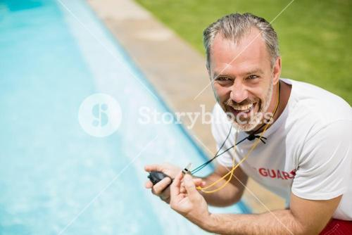 Portrait of swim coach holding stopwatch near poolside