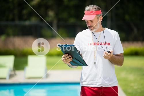 Swim coach looking at clipboard near poolside