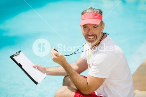 Portrait of swim coach holding stopwatch and clipboard near poolside