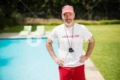 Portrait of swim coach with stopwatch standing with hands on hip near poolside