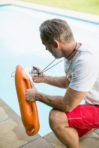Swim coach looking at stop watch and holding inflatable tube