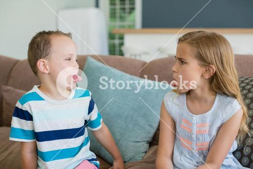 Sister and brother stick out tongues to each other on couch in living room